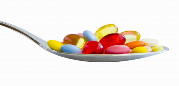 Colorful pills on spoon